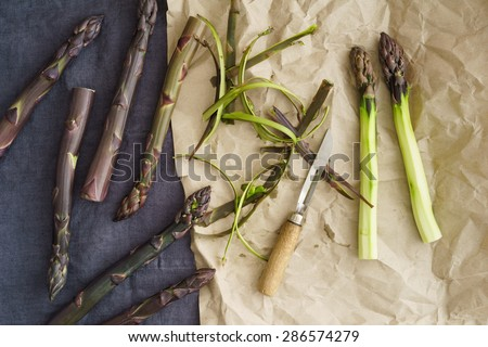 Fresh purple asparagus on paper with vintage peeling knife