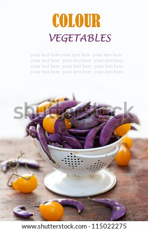Fresh purple beans and yellow tomatoes in the white colander with space for text. - stock photo