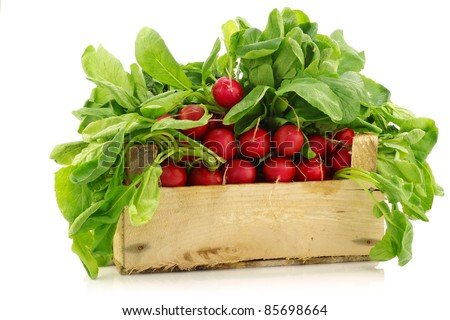 fresh radishes in a wooden crate on a white background