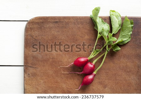 Fresh radishes on a wooden cutting board, over a white wooden table - stock photo