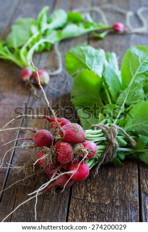 Fresh radishes on old wooden table bundle - stock photo