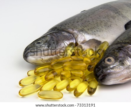 Fresh Rainbow trout and fish oil capsules - stock photo