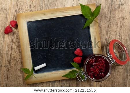 Fresh raspberries jam with chalkboard. Selective focus. - stock photo