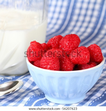 Fresh raspberries with milk and a spoon - stock photo