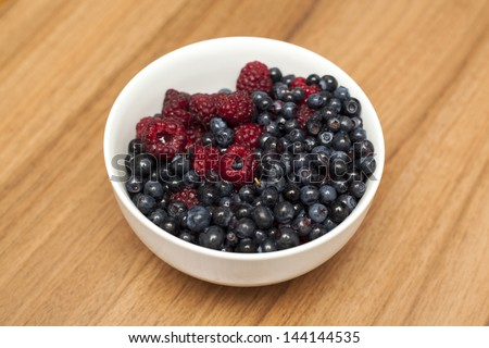 Fresh raspberry and blueberry in a white bowl on a wooden background