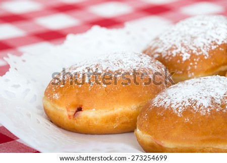 Fresh raspberry filled donuts topped with powdered sugar on a plate. Shallow depth of field.  - stock photo