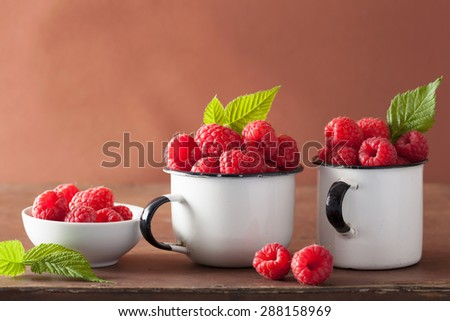 fresh raspberry in enamel cups over wooden background - stock photo