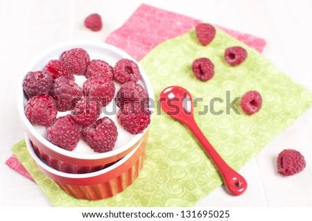 Fresh raspberry with cream or yogurt dessert top view - stock photo