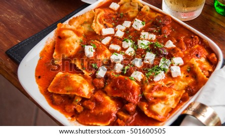 Fresh Ravioli with tomato sauce decorated with basil. Restaurant background