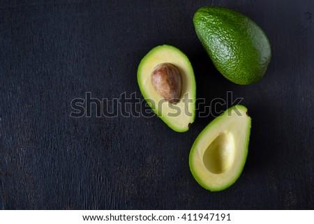 Fresh, raw avocado on a black background - stock photo