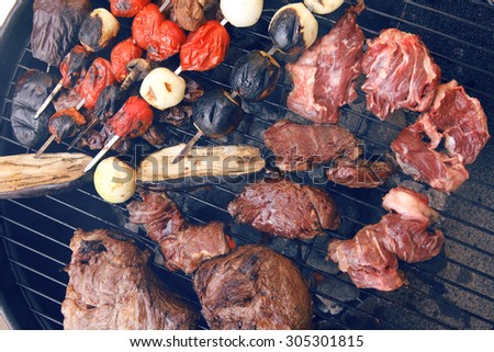 fresh raw beef fillet steak red meat with tomatoes and eggplant on skewers on big round barbecue brazier grid full with ready charcoal - stock photo