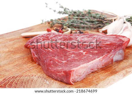 fresh raw beef meat fillet flesh with peppercorn and thyme ready to grill on wood board isolated over white background - stock photo