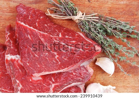 fresh raw beef meat fillet flesh with peppercorn and thyme ready to grill on wood figured old style board isolated over white background - stock photo