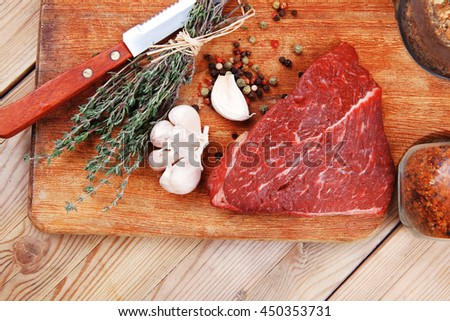 fresh raw beef meat fillet flesh with peppercorn and thyme ready to grill on wood figured old style board  over table with spices in glass - stock photo