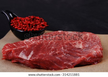 fresh raw beef meat marble steak on paper with saucer full pink peppercorn spice over black wooden table - stock photo