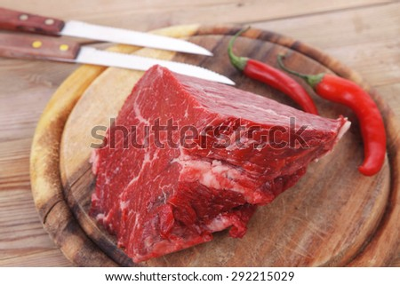 fresh raw beef meat steak chunk with red hot pepper on wood with stainless steel knife - stock photo