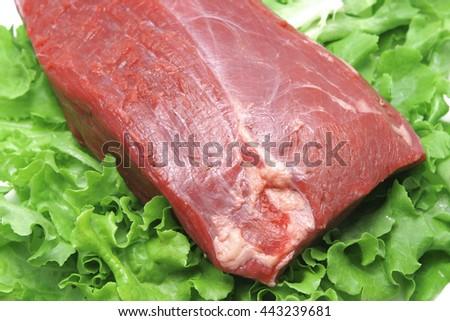 fresh raw beef on green salad - stock photo