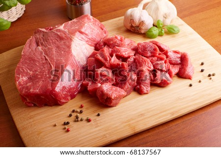 Fresh raw beef on wooden cutting board with garlic, pepper and basil - stock photo
