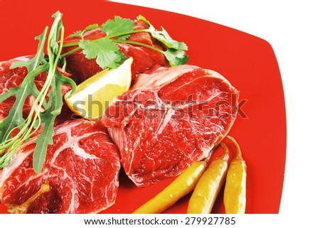 fresh raw beef red meat fillet medallion chunks on red plate isolated over white background - stock photo