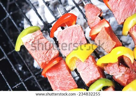 fresh raw beef shish kebab with pepper chunk on black big grill bbq - stock photo