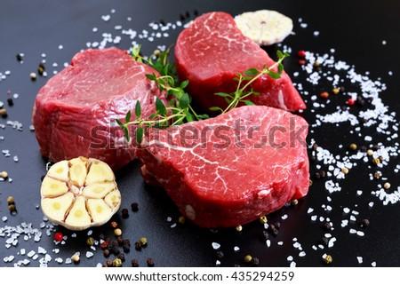 Fresh Raw Beef steak Mignon, with salt, peppercorns, thyme, garlic. - stock photo