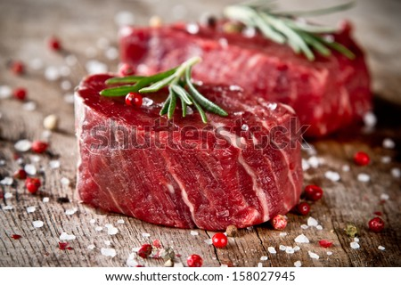Fresh raw beef steak on wood - stock photo