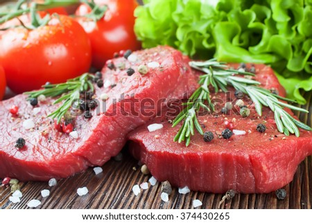 Fresh raw beef steak with spice and vegetable on brown wooden table