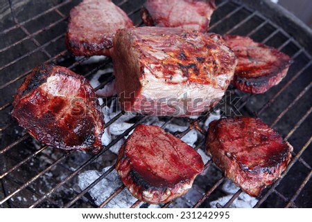 fresh raw big beef fillet chunk with roast slices on charcoal bbq grill - stock photo