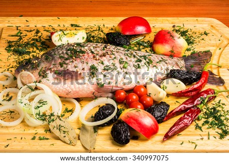 Fresh raw carp with vegetables, fruits and spices on wooden board. - stock photo