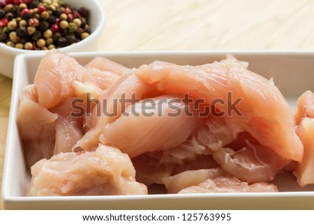 Fresh raw chicken in white bowl with whole pepper on table. Selective focus.