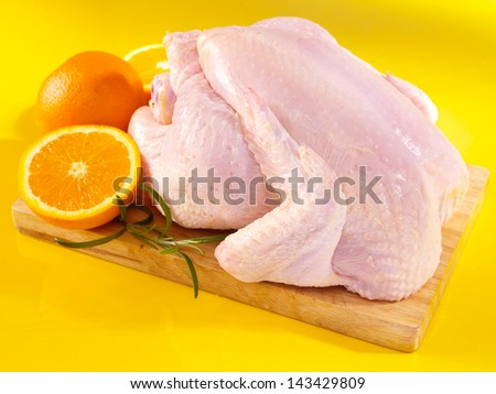 Fresh raw chicken on cutting board with oranges - stock photo