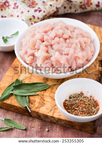 Fresh raw chopped chicken meat in a bowl with seasoning and sage, selective focus - stock photo
