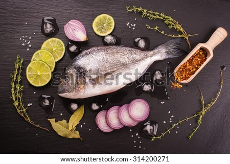 Fresh raw dorado fish with lime, red onion, spices and herbs over black stone background. Selective focus. Top view - stock photo