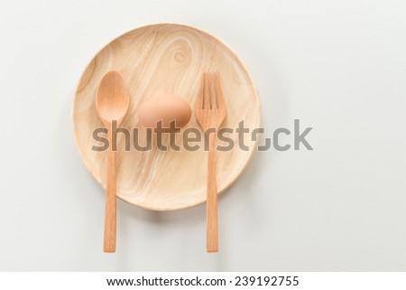 Fresh raw eggs isolated on wood dish over white background - stock photo