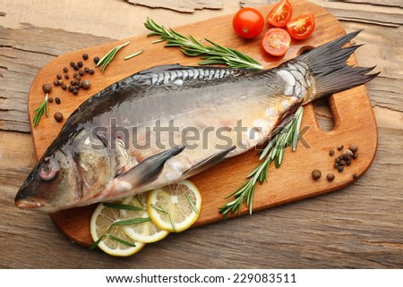 Fresh raw fish and food ingredients on table - stock photo