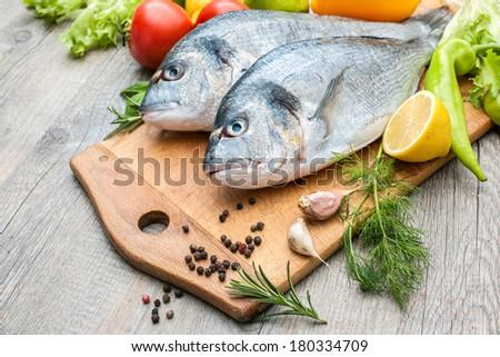 Fresh raw fish gilt head bream  a cutting board - stock photo