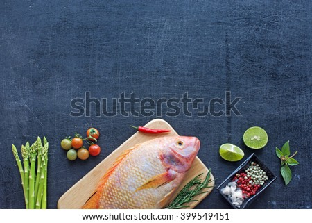 Fresh raw fish (Nile tilapia) with herbs and spices. Farm vegetables (asparagus, cherry tomato). Dark background. Copy space.  - stock photo