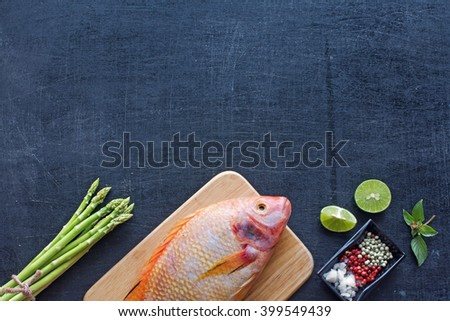Fresh raw fish (Nile tilapia) with lime, herbs, spices and asparagus. Dark background. Copy space.  - stock photo