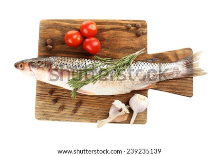 Fresh raw fish on cutting board and food ingredients isolated on white - stock photo