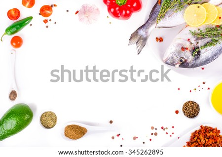 Fresh raw gilthead fishes with lemon, herbs, olive oil, avocado, paprika, herry tomatoes, garlic, salt on white background. Healthy food concept. Food frame. Free space for your text - stock photo