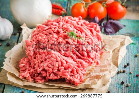fresh raw ground beef on a paper on a rustic wooden table - stock photo