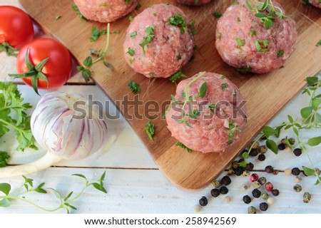Fresh raw meat balls with herbs - stock photo