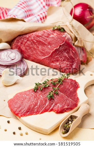 Fresh raw meat for cooking with thyme, onion and spices - stock photo