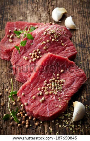 fresh raw meat for steak on wooden cutting board - stock photo