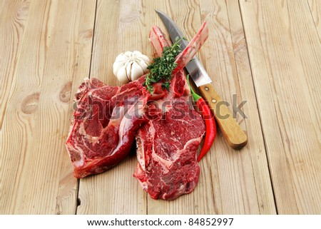 fresh raw meat : fresh red beef ribs with thyme , garlic and red chili pepper over wooden table - stock photo