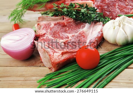 fresh raw meat : fresh red beef ribs with thyme , red chili pepper , cherry tomato , and garlic on wooden board - stock photo