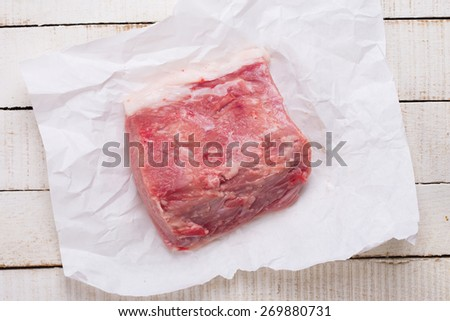 Fresh raw meat on paper on white painted  table. Selective focus. - stock photo
