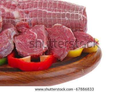 fresh raw meat on wooden board with slices - stock photo