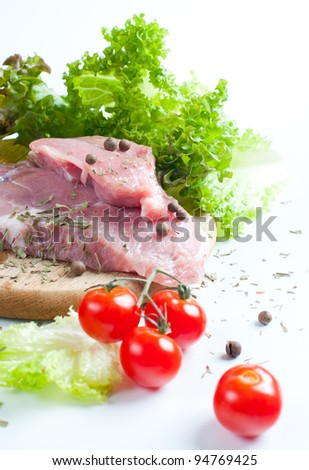 Fresh raw meat, tomatoes and a salad on white background