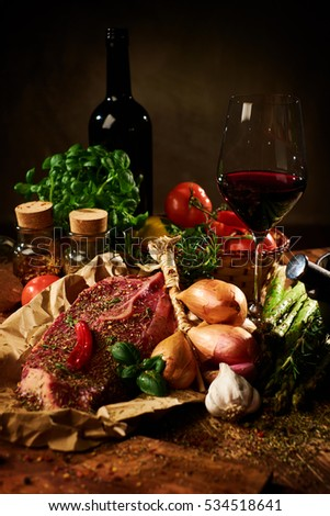 Fresh raw meat with herbs, glass of red wine and vegetables